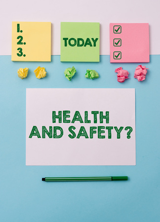Writing note showing Health And Safety Question. Business concept for regulations and procedures to prevent accident or injury Note papers and stationary placed sideways on top of softhued backdrop 版權商用圖片