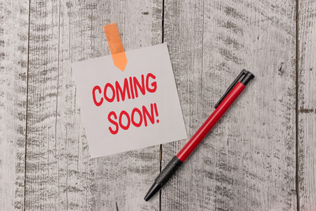 Text sign showing Coming Soon. Business photo text event or action that will happen after really short time One plain blank paper sheet and a pen attached with wooden textured table