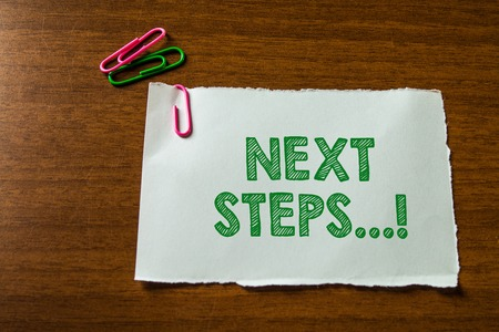 Word writing text Next Steps. Business photo showcasing something you do after you have finished doing first one Close up blank stationary paper hold three colored clips lying wooden table 写真素材