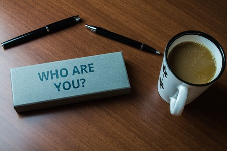 Word writing text Who Are You question. Business photo showcasing asking about demonstrating identity or demonstratingal information Upper close view two ball point pens case set coffee cup lying wooden table Stock fotó