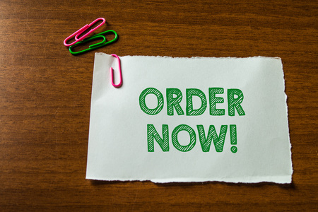 Word writing text Order Now. Business photo showcasing confirmed request by one party to another to buy sell Close up blank stationary paper hold three colored clips lying wooden table