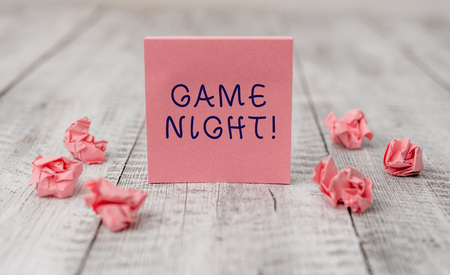 Handwriting text writing Game Night. Conceptual photo usually its called on adult play dates like poker with friends Thick set of plain note paper with scraps on the wooden textured table 스톡 콘텐츠