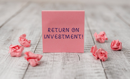 Handwriting text writing Return On Investment. Conceptual photo perforanalysisce measure used evaluate efficiency of investment Thick set of plain note paper with scraps on the wooden textured table 写真素材