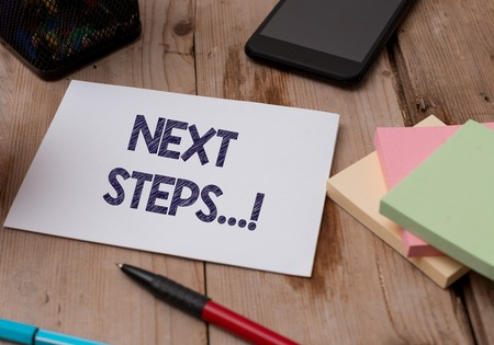 Word writing text Next Steps. Business photo showcasing something you do after you have finished doing first one Top view wooden table stationary paper tablet pen colored stick pad notes Stock Photo
