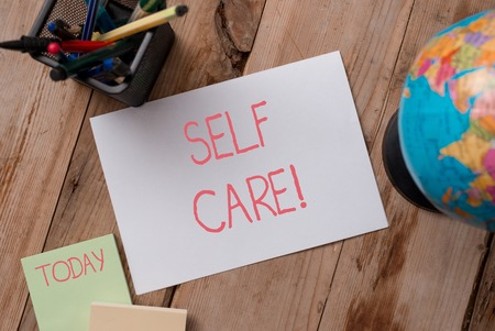 Writing note showing Self Care. Business concept for practice of taking action to preserve or improve ones own health Writing equipments and sheets with artificial globe on the wooden desk