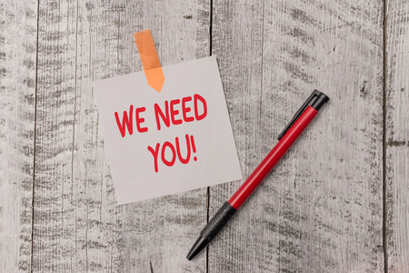Text sign showing We Need You. Business photo text asking someone to work together for certain job or target One plain blank paper sheet and a pen attached with wooden textured table