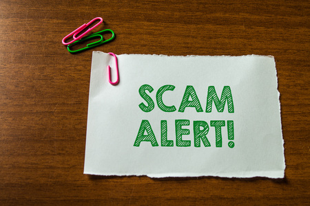 Word writing text Scam Alert. Business photo showcasing fraudulently obtain money from victim by persuading him Close up blank stationary paper hold three colored clips lying wooden table