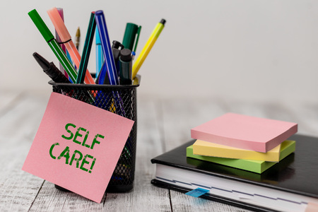 Handwriting text Self Care. Conceptual photo practice of taking action to preserve or improve ones own health Writing equipment and note paper sheets with agenda book on the wooden desk