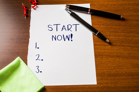 Text sign showing Start Now. Business photo showcasing do not hesitate get working or doing stuff right away Blank stationary paper wooden table fountain pen cloth rag pins to fix