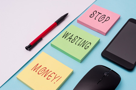 Word writing text Stop Wasting Money. Business photo showcasing advicing demonstrating or group to start saving and use it wisely Note papers and stationary plus gadgets placed sideways above backdrop