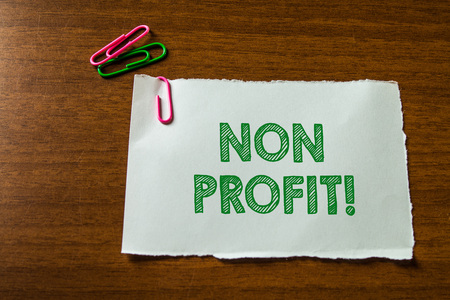 Word writing text Non Profit. Business photo showcasing not making or conducted primarily to make profit organization Close up blank stationary paper hold three colored clips lying wooden table 写真素材