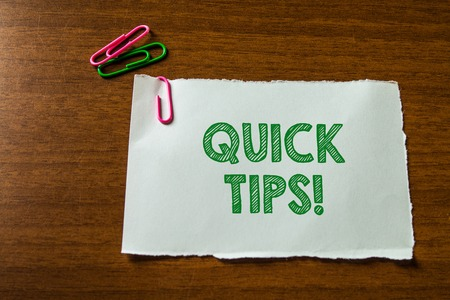 Word writing text Quick Tips. Business photo showcasing small but particularly useful piece of practical advice Close up blank stationary paper hold three colored clips lying wooden table