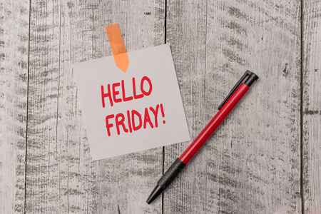 Text sign showing Hello Friday. Business photo text used to express happiness from beginning of fresh week One plain blank paper sheet and a pen attached with wooden textured table Stock Photo