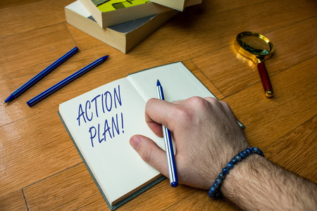 Word writing text Action Plan. Business photo showcasing proposed strategy or course of actions for certain time Close up view man writing notebook pen set lying wooden table two books Stock Photo