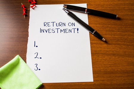 Text sign showing Return On Investment. Business photo showcasing perforanalysisce measure used evaluate efficiency of investment Blank stationary paper wooden table fountain pen cloth rag pins to fix Stock Photo