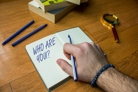 Word writing text Who Are You Question. Business photo showcasing asking about someone identity or demonstratingal information Close up view man writing notebook pen set lying wooden table two books