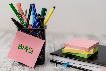 Handwriting text Bias. Conceptual photo inclination or prejudice for or against one demonstrating group Writing equipment and note paper sheets with agenda book on the wooden desk