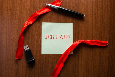 Text sign showing Job Fair. Business photo showcasing event in which employers recruiters give information to employees USB memory lying wooden table square blank note stripes ribbon up down pen