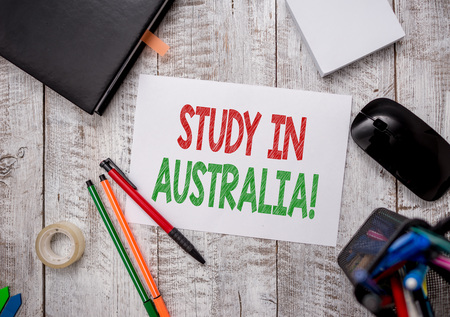 Writing note showing Study In Australia. Business concept for going into foreign country order complete your studies Stationary and computer stuff pen with paper sheets on desk