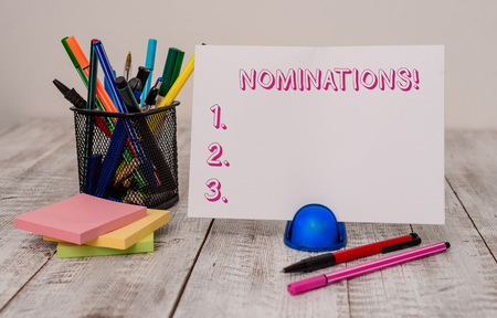 Writing note showing Nominations. Business concept for action of nominating or state being nominated for prize Stationary and computer mouse with globe on the wooden desk