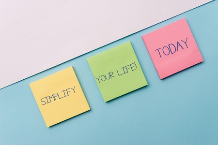 Text sign showing Simplify Your Life. Business photo showcasing focused on important and let someone else worry about less ones Pastel colour note papers placed sideways on the of softhued backdrop Foto de archivo