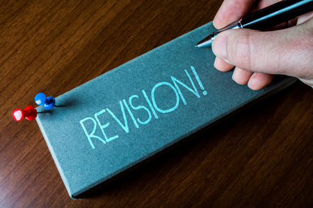 Writing note showing Revision. Business concept for action of revising over someone like auditing or accounting Close up left man right hand holding pen fixed pins lying wooden table