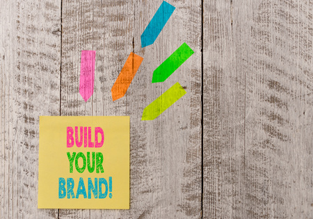 Conceptual hand writing showing Build Your Brand. Concept meaning creates or improves customers knowledge and opinions of product Note paper and line arrow stickers on the top of wooden table desk