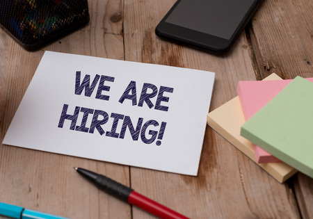 Word writing text We Are Hiring. Business photo showcasing recently you employ someone or pay someone to do particular job Top view wooden table stationary paper tablet pen colored stick pad notes Stock Photo