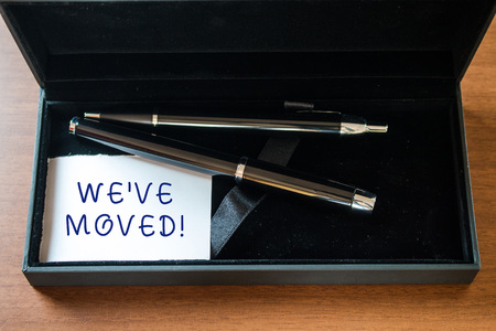 Writing note showing We Ve Moved. Business concept for having strong feelings sadness or sympathy has said or done Close up case ball point fountain pens set blank card lying on wooden