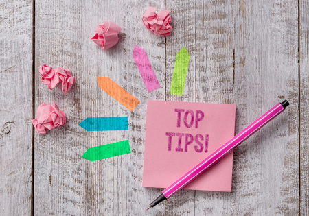 Conceptual hand writing showing Top Tips. Concept meaning small but particularly useful piece of practical advice Note paper and line arrow stickers on the top of wooden table desk Stock fotó