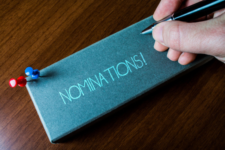 Writing note showing Nominations. Business concept for action of nominating or state being nominated for prize Close up left man right hand holding pen fixed pins lying wooden table