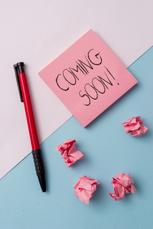 Writing note showing Coming Soon. Business concept for event or action that will happen after really short time Note papers and stationary placed sideways on top of softhued backdrop