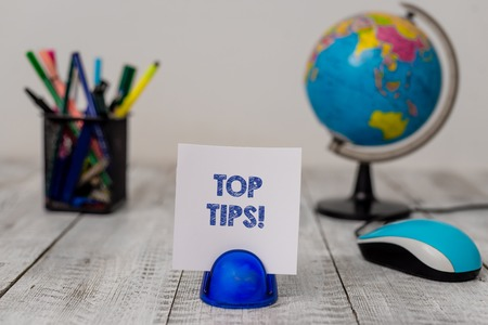 Conceptual hand writing showing Top Tips. Concept meaning small but particularly useful piece of practical advice Stationary and computer mouse with globe on the wooden desk