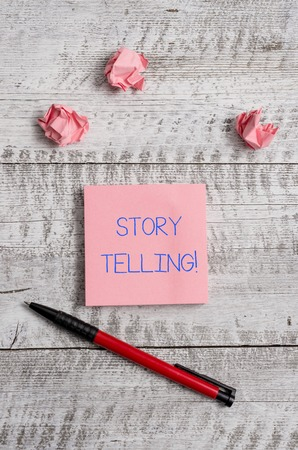 Conceptual hand writing showing Storytelling. Concept meaning activity writing stories for publishing them to public Stationary and paper scraps with sheets on the wooden desk