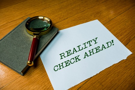 Text sign showing Reality Check Ahead. Business photo text makes them recognize truth about situations or difficulties Close up electronic device gadget magnifying glass resting wooden table