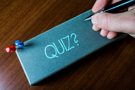Writing note showing Quiz Question. Business concept for test of knowledge as competition between individuals or teams Close up left man right hand holding pen fixed pins lying wooden table Stock Photo