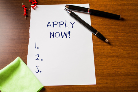 Text sign showing Apply Now. Business photo showcasing request something officially in writing or by sending in form Blank stationary paper wooden table fountain pen cloth rag pins to fix
