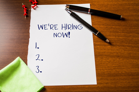 Text sign showing We Re Hiring Now. Business photo showcasing recently employ someone or pay someone to do particular job Blank stationary paper wooden table fountain pen cloth rag pins to fix