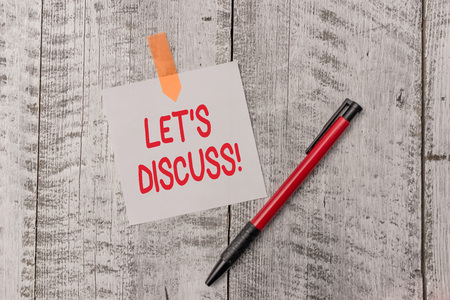 Text sign showing Let S Discuss. Business photo text asking someone to talk about something with demonstrating or showing One plain blank paper sheet and a pen attached with wooden textured table