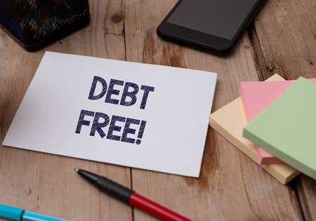 Word writing text Debt Free. Business photo showcasing does not owning any money or things to any individual or companies Top view wooden table stationary paper tablet pen colored stick pad notes