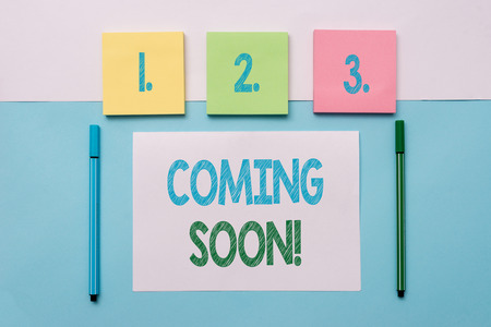 Text sign showing Coming Soon. Business photo text event or action that will happen after really short time Note papers and stationary placed sideways on top of softhued backdrop Imagens