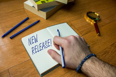 Word writing text New Release. Business photo showcasing announcing something newsworthy recent product Close up view man writing notebook pen set lying wooden table two books