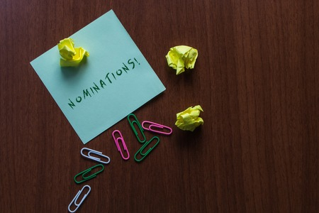 Word writing text Nominations. Business photo showcasing action of nominating or state being nominated for prize Upper view three small paper balls colored clips stick pad wooden table Stock Photo
