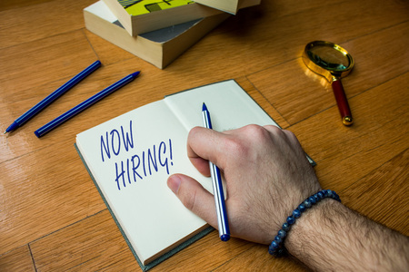 Word writing text Now Hiring. Business photo showcasing finding evaluating working relationship with future employees Close up view man writing notebook pen set lying wooden table two books