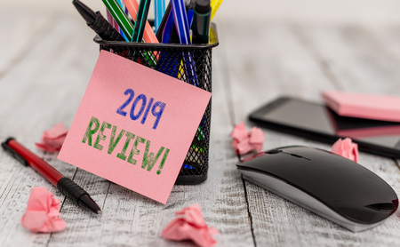 Word writing text 2019 Review. Business photo showcasing remembering past year events main actions or good shows Writing equipment and paper plus scraps with gadgets on the wooden desk Stock Photo