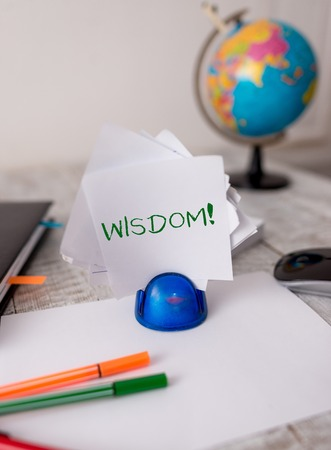 Word writing text Wisdom. Business photo showcasing quality having experience knowledge and good judgement something Stationary and computer stuff plus pen with paper sheets on the wooden desk Stock Photo