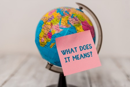 Word writing text What Does It Means question. Business photo showcasing asking meaning something said and do not understand Plain note paper sticked to a mini miniature of the world on the wooden table