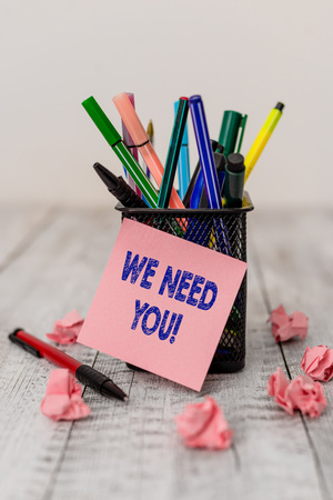 Writing note showing We Need You. Business concept for asking someone to work together for certain job or target Writing equipment and paper scraps with blank sheets on the wooden desk