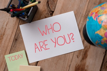 Writing note showing Who Are You question. Business concept for asking demonstrating identity or demonstratingal information Writing equipments and sheets with artificial globe on the wooden desk