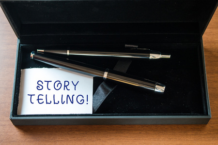 Writing note showing Storytelling. Business concept for activity writing stories for publishing them to public Close up case ball point fountain pens set blank card lying on wooden